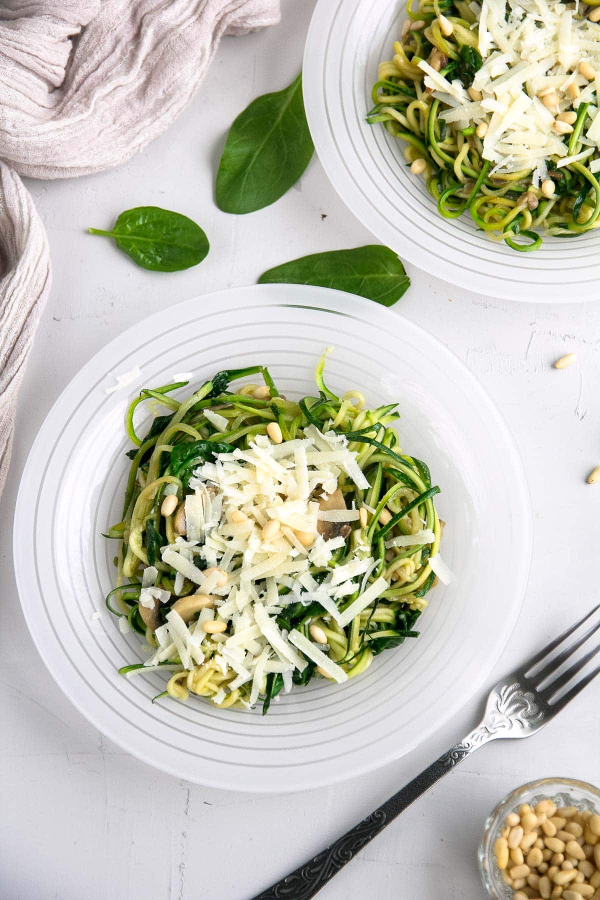 Two plates of a spinach, mushroom, parmesan zoodles recipe.