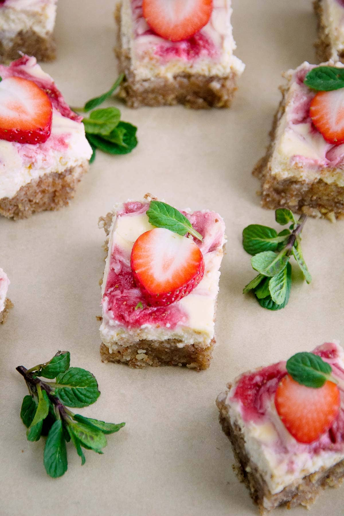 Freshly baked strawberry cheesecake recipe cut into squares.