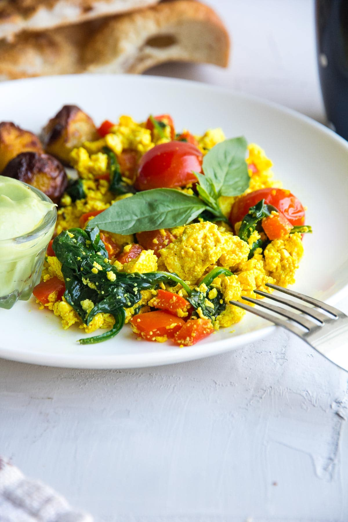Healthy vegan tofu scramble recipe with spinach and tomatoes.