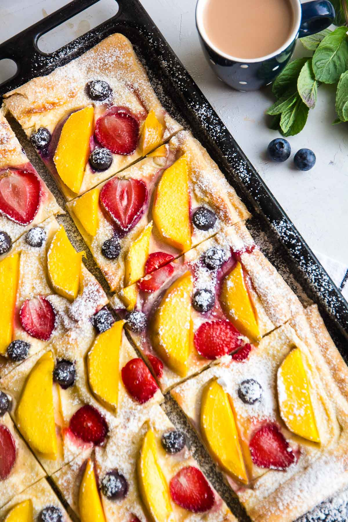 A tray of a freshly baked vegan fruit tart recipe with slices of mangoes, strawberries, and blueberries.