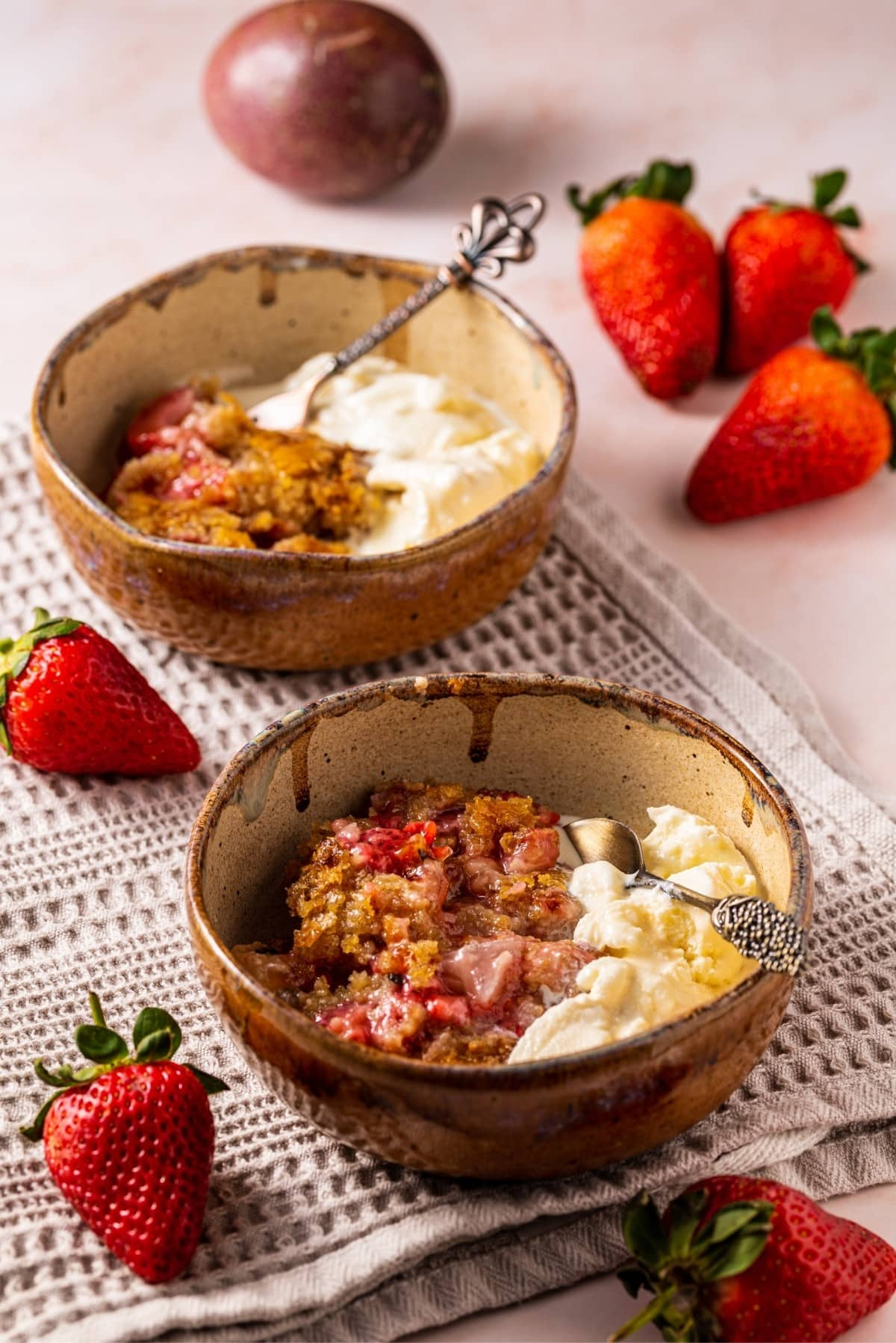 Two bowls of paleo strawberry passion fruit cobbler recipe and vanilla ice cream.