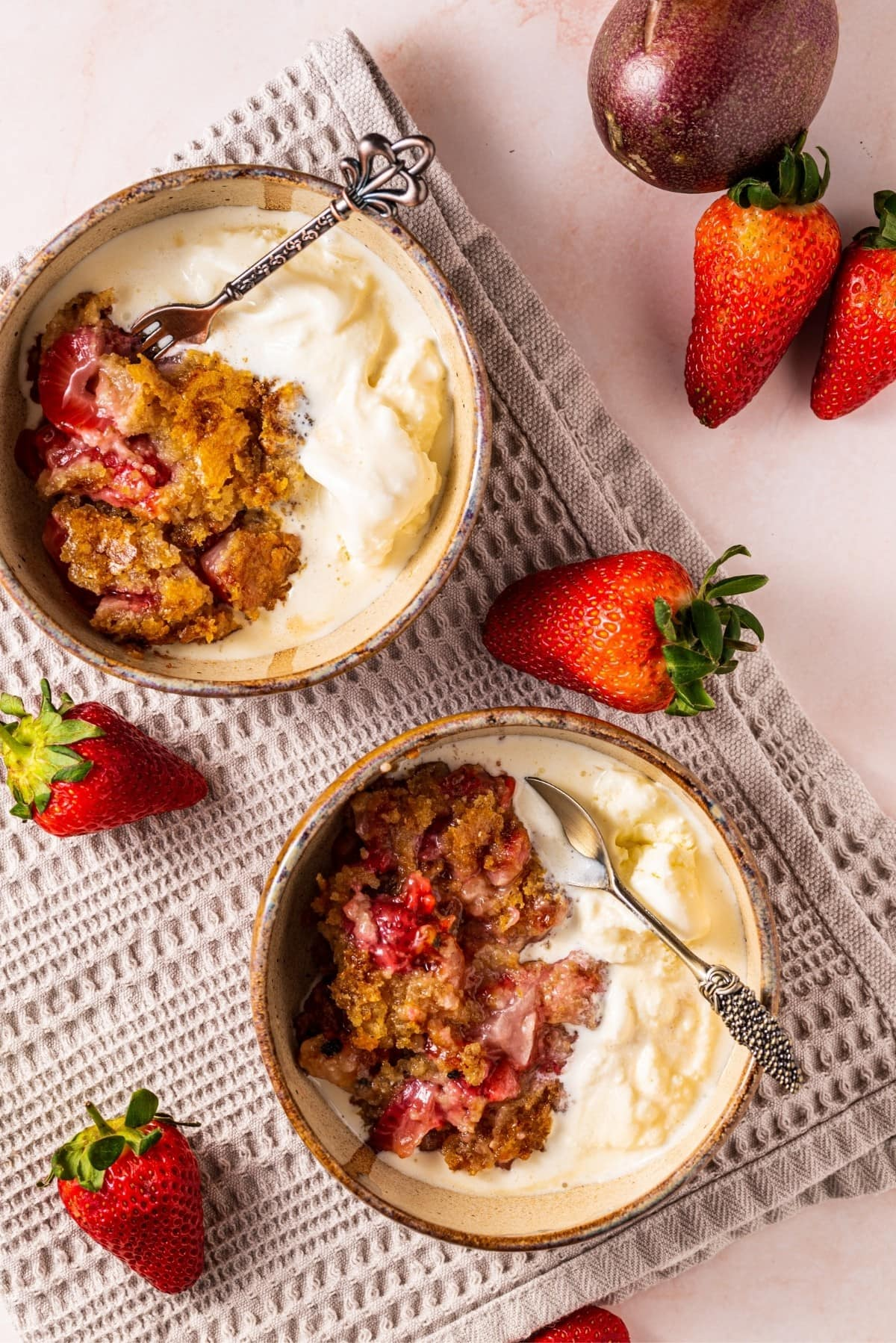 Two bowls of paleo strawberry passion fruit cobbler served with vanilla ice cream.