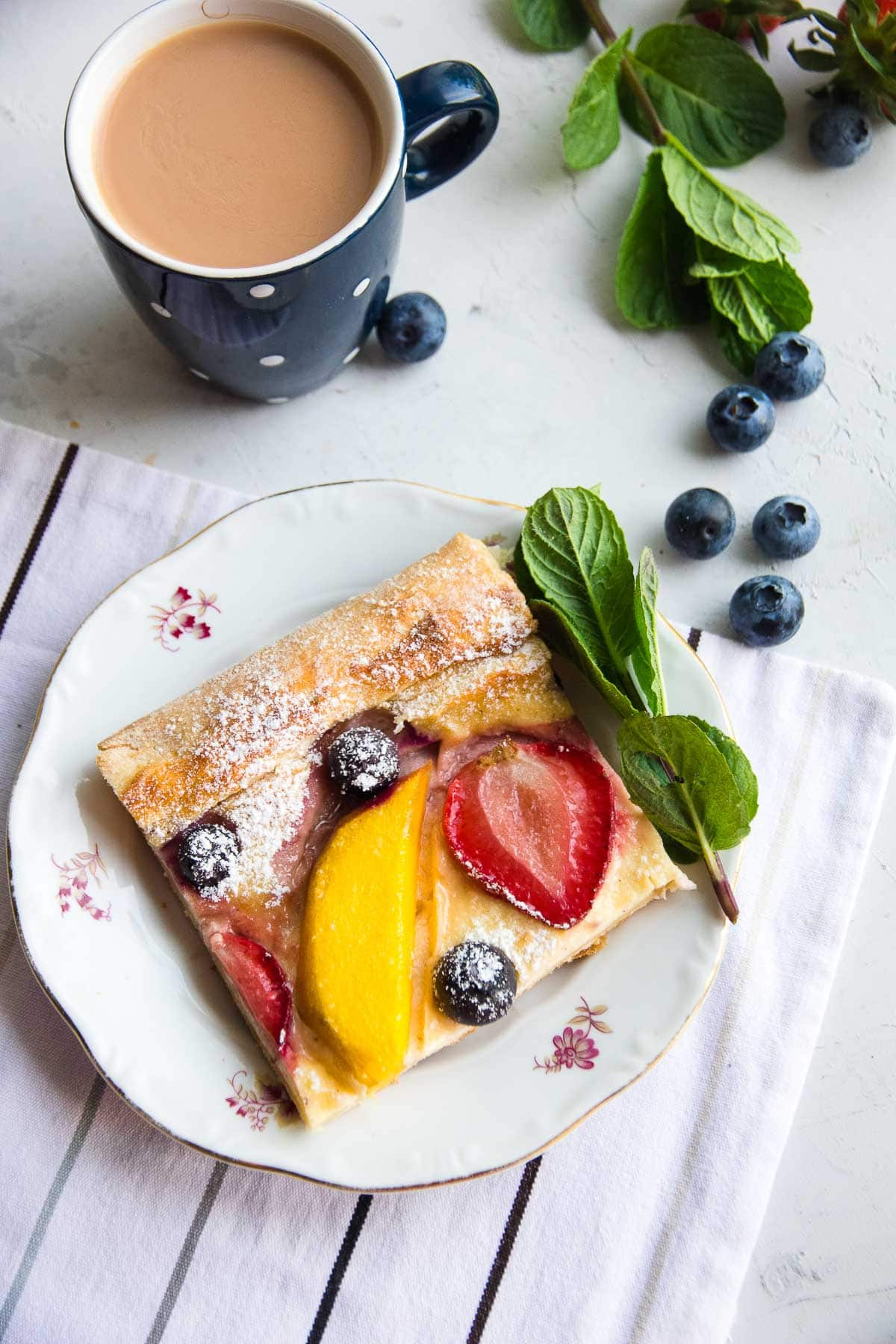 A slice of a healthy vegan fruit tart recipe made with mangoes, strawberries, and blueberries.