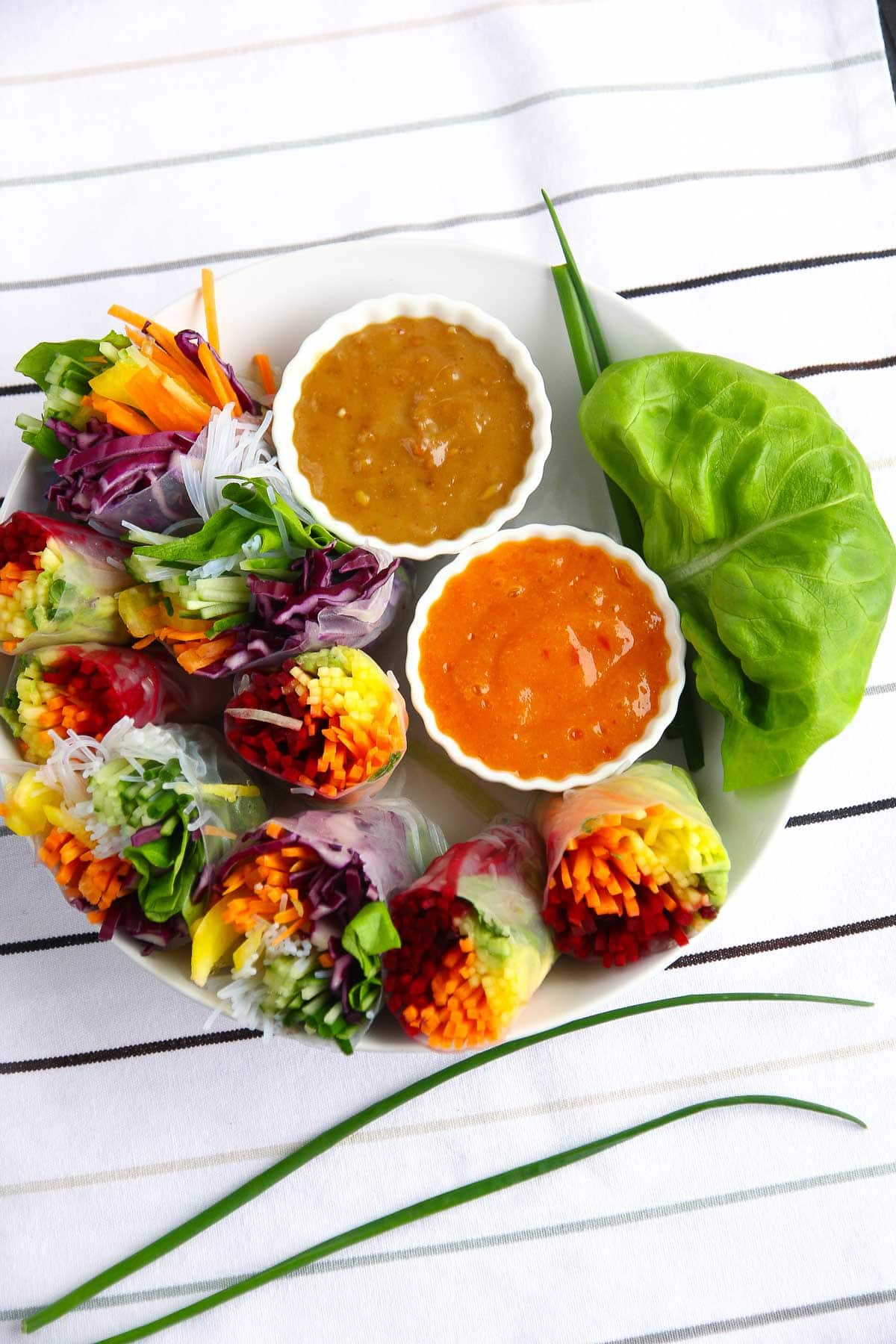 Vegan rainbow spring rolls on a platter with two dipping sauces - mango chili and a peanut ginger.