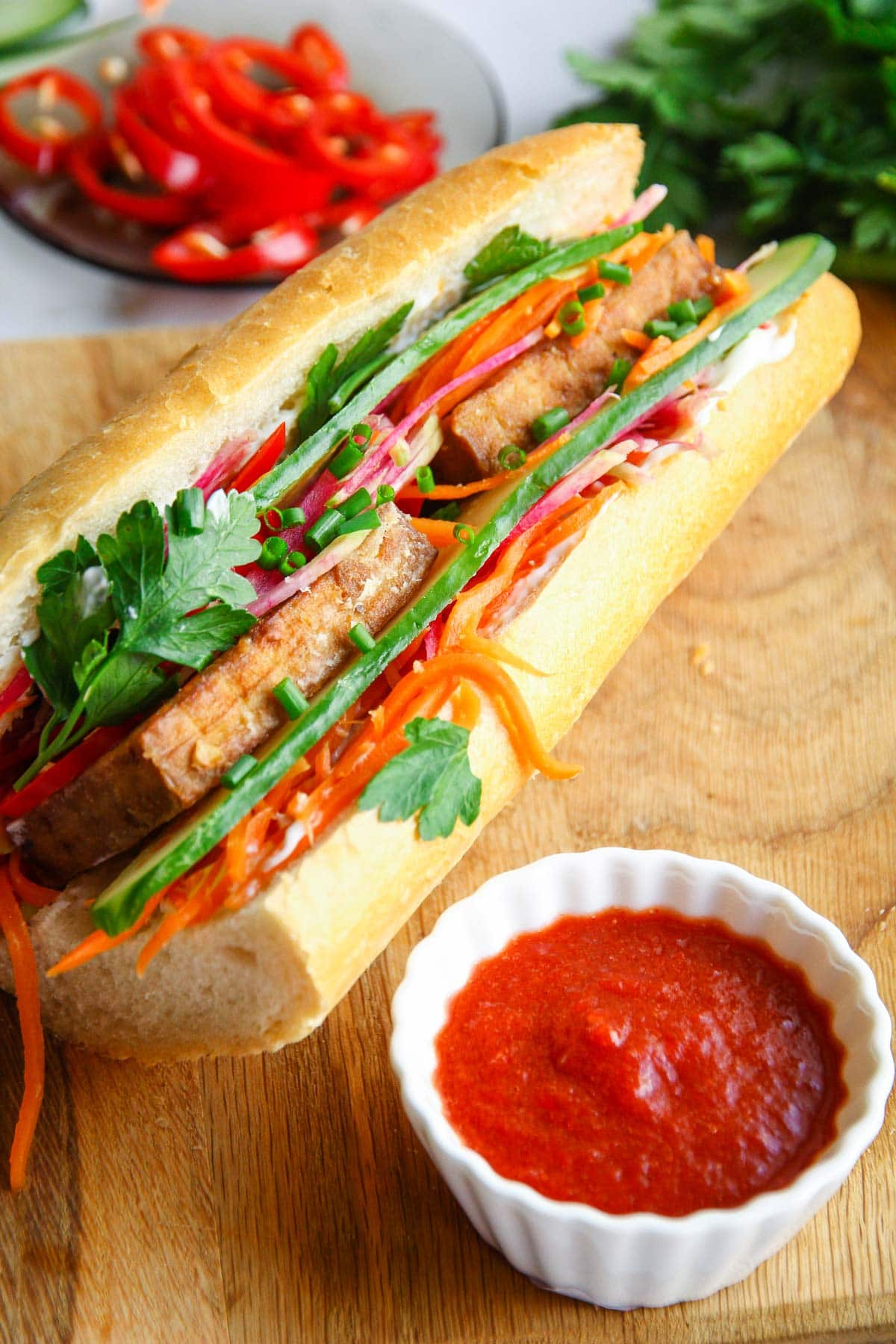 A healthy vegan banh mi sandwich made with tofu and fresh vegetables and a sriracha dipping sauce.