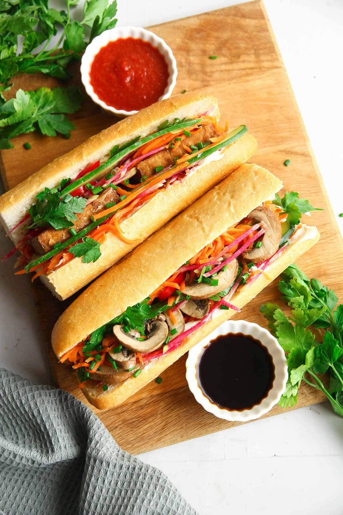 Two vegan banh mi sandwiches made with tofu and mushrooms and filled with pickled vegetables.