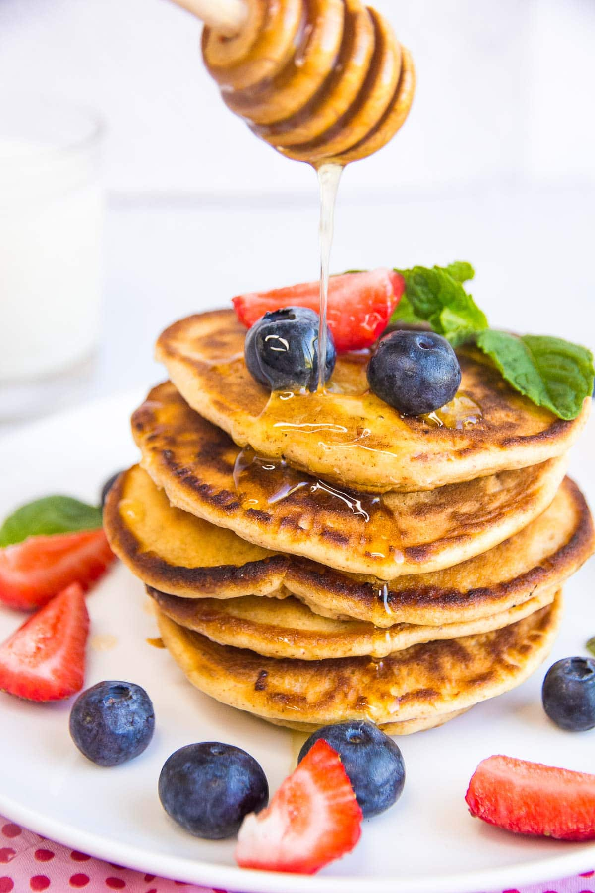 Sugar-free syrup being poured on a stack of keto almond flour pancakes with fresh berries.